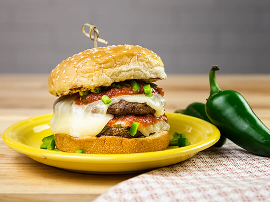 Green-chili burger on a yellow plate with two jalapeno peppers