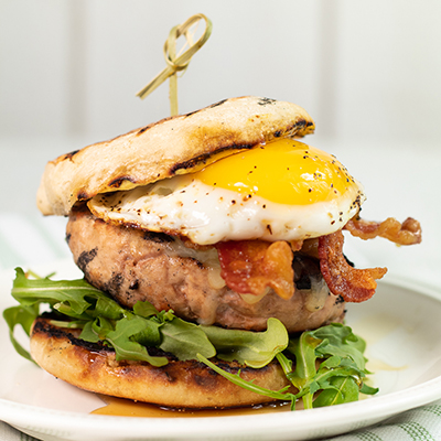 Stew's Breakfast turkey burger with a bacon and arugula topped with a fried egg and english muffins.