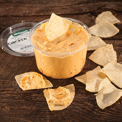 Buffalo chicken dip with tortilla chips on a dark wood background