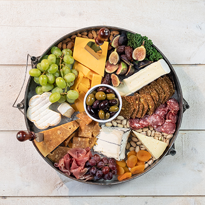A photo of a cheese plate with various cheeses, crackers, meat and fruit.