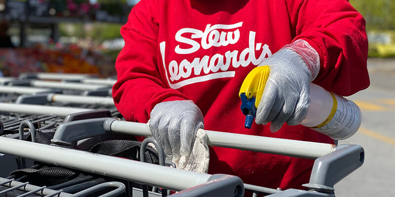A Stew Leonard's Team Member sanitizing our shopping carts.