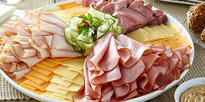 A selection of deli sliced meats and cheeses on a white plate
