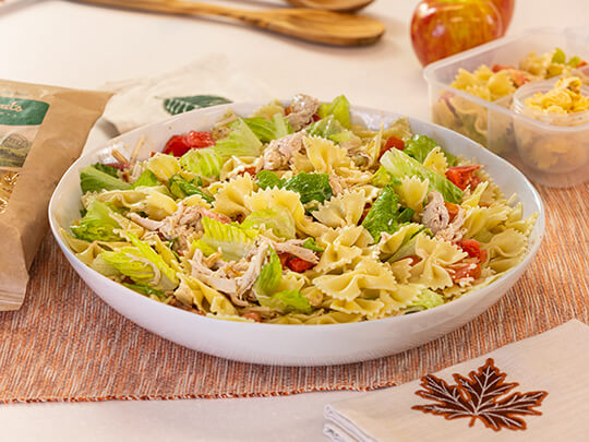 Farfalle pasta salad with chicken, tomatoes and romaine lettuce in a white bowl sitting on a fall themed placemat