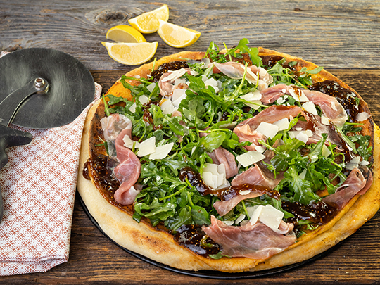 Grilled pizza with fig spread, parmesan, prosciutto and arugula on a wooden cutting board.