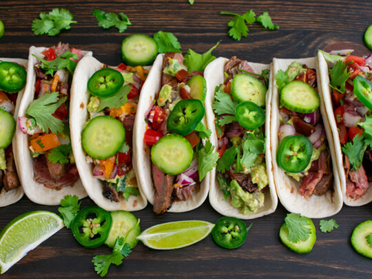 Flank steak tacos garnished with hot peppers, cucumbers, red onions and orange peppers surrounded by lime wedges on a brown table