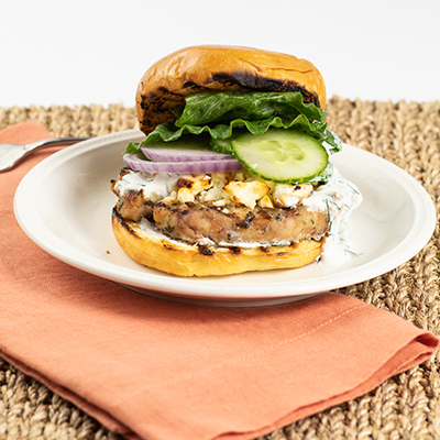 A chicken burger on top of a brioche bun topped with feta cheese, cucumbers, onions, greek yogurt and lettuce.