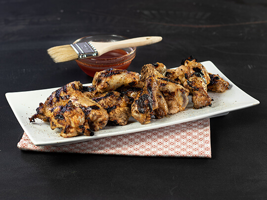 Grilled chicken wings rest on a white plate on top of a dark table. A cup of barbecue sauce is in the background.