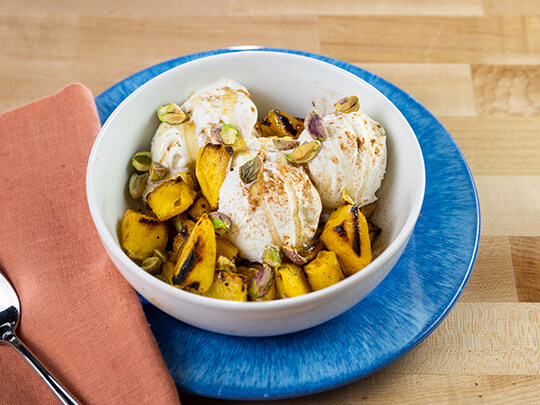 Grilled honey glazed mangoes in a white bowl covered with vanilla ice cream.