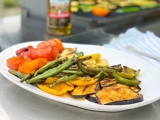 Grilled fresh summers vegetables on a white plate with a bottle of Stew Leonard's olive oil