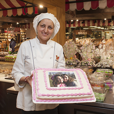 A bakery team member holding one of our delicious photo cakes.