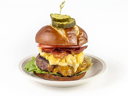 A bacon, mac and cheese burger on a pretzel roll. Photographed on a white background