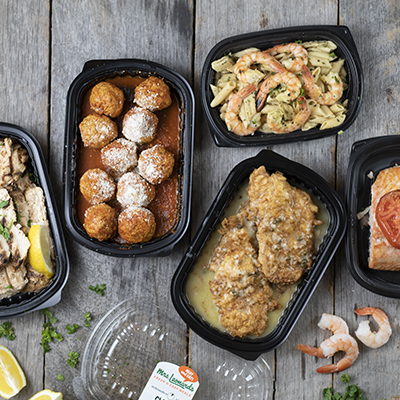 A selection of prepared meals including meatballs, grilled shrimp and chicken.