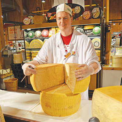 A Stew Leonard's Team Member holding a wheel of Jarlsberg cheese.