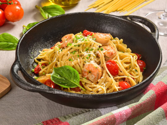 Photo of a cast iron skillet with linguini and shrimp