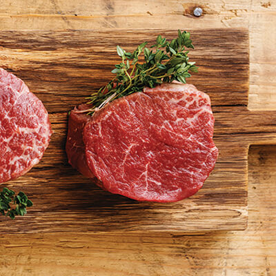 Raw filet mignon steaks on a wooden butcher block.