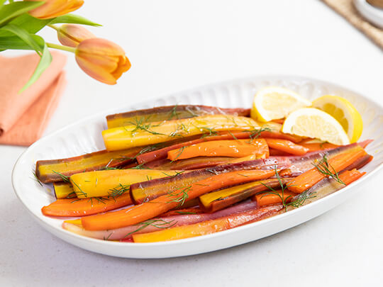 A photo of carrots on a white plate with dill and lemon wedges