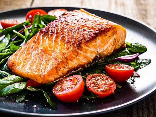Fried salmon steak with vegetables on wooden table