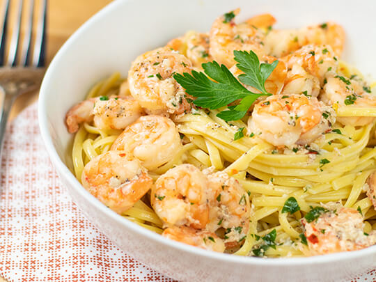 Shrimp scampi in a white bowl with pasta on a patterned placemat
