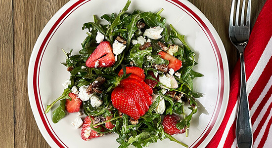 Arugala and strawberry salad on a white plate