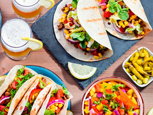 Table with tacos, mango salsa, nachos with sauce, guacamole, lemon beer for Cinco de Mayo celebration party. Appetizers and traditional mexican dishes for family dinner on wooden table