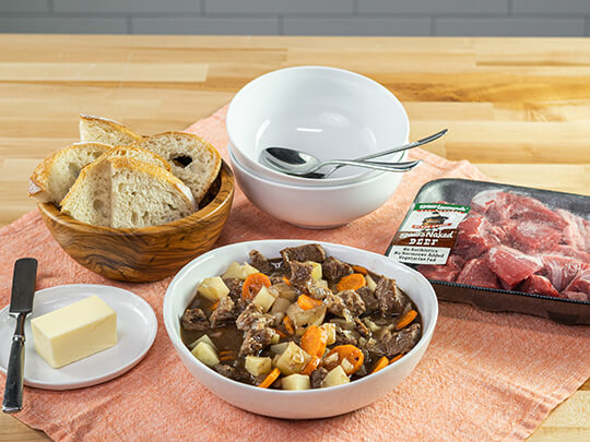 A bowl of beef stew on a table with bread, butter and a package of beef stew meat in the background