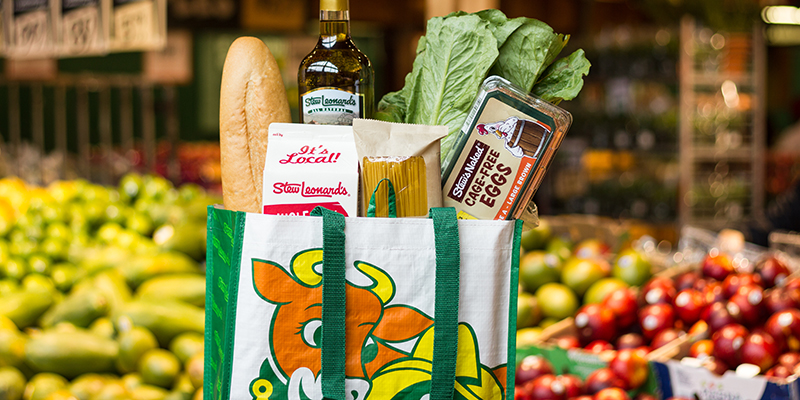 A Stew Leonard's reusable bag filled with groceries with fresh produce in the background.