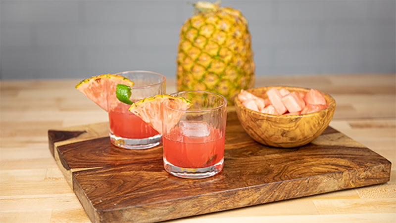 Two cocktail glasses with our pink pineapple cocktail on a cutting board with a bowl of pink pineapple and a whole pineapple in the background