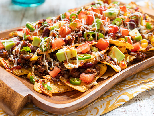Mexican nacho yellow corn tortilla chips with cheese, meat, avocado guacamole and red hot spicy salsa