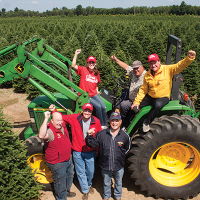 A photo of Stew Jr. and our team members visiting our Christmas Tree farm in Canada.
