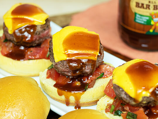 Three beef sliders with BBQ sauce, cheddar cheese and pico de gallo