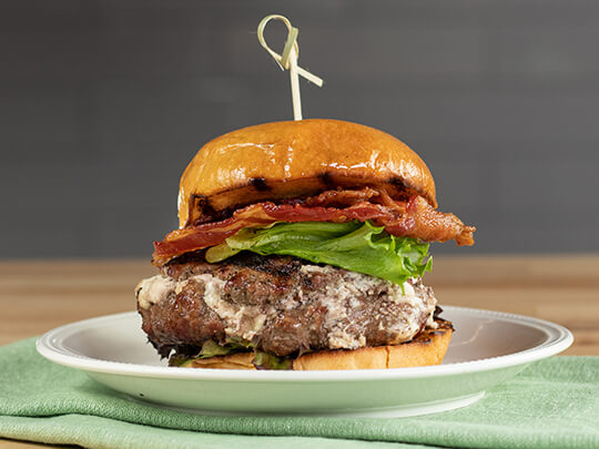 Goat cheese stuffed burger topped with lettuce and bacon between brioche rolls.