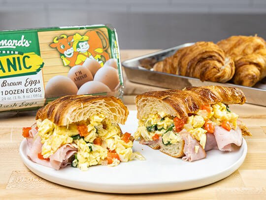 Egg, ham and spinach croissant sandwiches on a white plate. A container of stew Leonard's Organic eggs and Stew's croissants are visible in the background