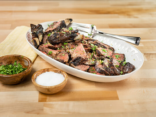 Marinated beef short ribs with cilantro on a white plate.