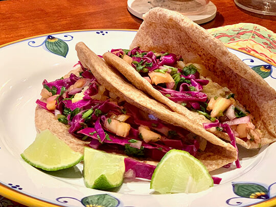 Two whole wheat fish tacos with pineapple slaw on a plate with lime wedges