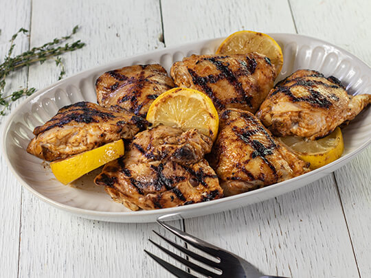 Grilled chicken thighs on a platter with sliced lemon. The platter is sitting on white barn board.