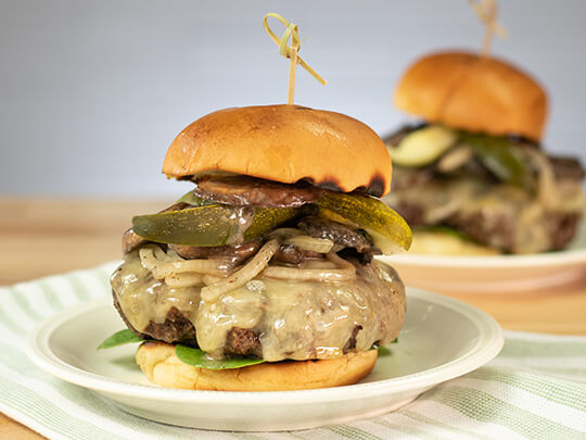 Mushroom and swiss cheeseburger with dill pickle, onions and mushrooms.