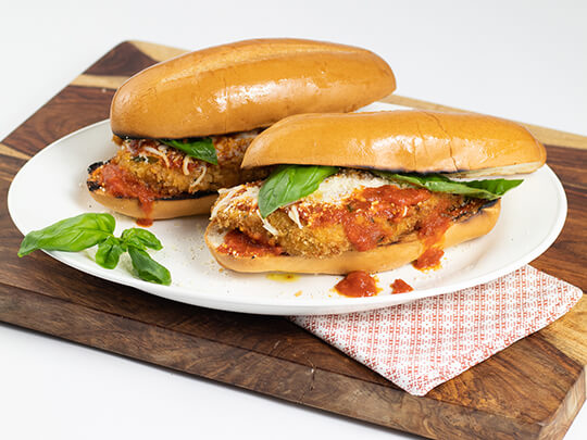 Two chicken parm grinders on grinder rolls with cheese and basil