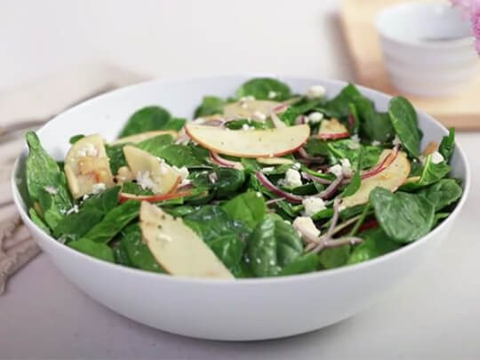 Spinach salad with sliced apples, toasted almonds and feta cheese in a white bowl